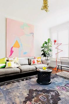 In the Melbourne apartment of artist Miranda Skoczek, a candy-colored painting by Rhys Lee is situated above a sofa from Aero Designs.