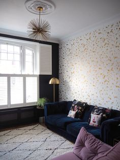 Create bold drama in your living room with a patterned wallpaper feature wall and deep blue walls with gold accents throughout the home decor. The simple white contrast of shutters in Jess's space ensure a light, bright feel in a moody interior.