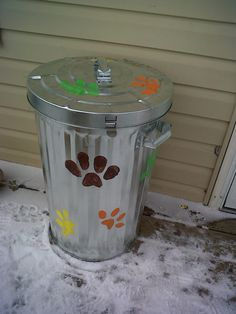 Steel garbage can with painted paw prints to hold dog food.  Critter, and element proof.  www.countrymom.scentsy.ca