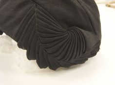 Fabric Manipulation for Fashion - decorative spiral pleats using arrowhead folds - close up photo of a pleated hat; couture sewing inspiration