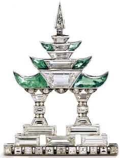 Diamond and emerald Pagoda brooch, Janesich, circa 1925. Photo Sotheby's.  Designed as a pagoda with stylized columns and upturned eaves, set with baguette, square-shaped, trapeze-cut, triangular-shaped, single-cut and rose-cut diamonds weighing approximately 3.00 carats, accented with 6 calibré-cut buff-top emeralds, mounted in platinum, signed JANESICH,