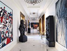 The entrance gallery displays highlights from the homeowners' collection, including paintings by Jean Dubuffet (left), Jean-Michel Basquiat (far wall), and Jim Dine (right); the sculptures are by (from left) Fernando Botero, Roy Lichtenstein, Bruce Nauman, and Louise Nevelson.  ARCHITECT: James Aman DESIGNER: Mark Stumer PHOTOGRAPHER: William Waldron