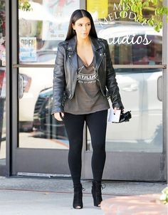 Kim Kardashian wears a cool rocker tee, black leggings, a leather jacket and heels