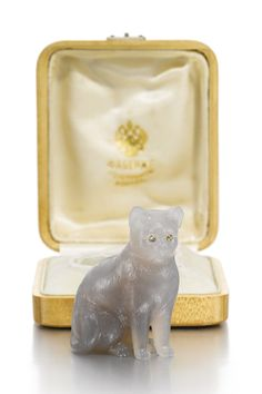 A Fabergé hardstone figure of a cat, circa 1900. Carved of chalcedony, sitting upright and alert, rose-cut diamond-set eyes.