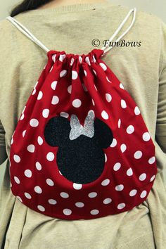 A Brand new creation by a member of our creative team....drawstring backpacks...great to haul your shoes, bows, whatever, around with you at cheerleading competitions, OR, a day out at an amusement park. This bag pictured, is being worn by an adult, so you get an idea of the size. Red and white polka dots, with this great glittery Minnie Mouse head and bow. Also available for groups and customized. Over 20 years in business !  Shipping is first class mail. If you need priority, please…