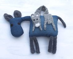 Beautiful, very friendly and nice donkey - everybody likes him! Sewn of blue denim and gray artificial fur, with eyes made of buttons. He has polyfill insert. And most important: the donkey has small donkey scarf! This scarf is made of light gray anf white yarn and has eyes made os buttons too!  The donkey can be uses as pillow for child (at home and during travel), as toy for kid or even as sleep mask for really big person!   Very soft and lovely!  Donkey size: Max. size (with ears and…
