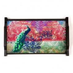 Neo Nawab Peacock Saga Tray : This Neo Nawab tray portrays a beautiful peacock gazing at the mahal with a beautiful scenic background. The rectangular tray is  is made of wood and has an elegant, royal shape handle.