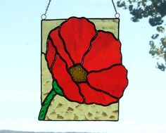 This large brilliant Red Poppy window hanging is made of a gorgeous red on red streaky transparent stained glass. The background glass is a beautiful softly textured amber glass. I have applied a dark patina to the soldered seams. It is 7 1/2 high, 6 1/4 wide. I will include a length of chain for hanging. (A suction cup for this item is not recommended; it will need to be hung from a nail or hook above the window.)       Images and design © copyright Ladybug Stained Glass