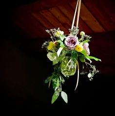 image of purple, yellow, and green floral arrangement in a fruit jar hanging by a tan ribbon from the ceiling - photo by New Mexico based wedding photographers Twin Lens