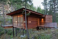 """830 square feet Andersson Wise Architects Polson, Montana Perched on pillars near a granite and slate outcrop in the pine forests of Montana, this small wood cabin blends nearly seamlessly with the picturesque landscape. The open plan is comfortable inside, and the wood floors extend to a deck and small bridge over the natural sloping terrain. The small house was built off site and installed with minimal disturbance to the land. It is off the grid and takes advantage of """"passive"""" heating and…"""