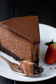 A slice of Nutella cheesecake on a white plate with fork holding a small bite.