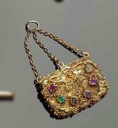 "An Antique Pendant with gold Foliate and Gemstones. The Gems spell out the word ""REGARD"" using their first letters - Ruby, Emerald, Garnet, Amethyst, Ruby, Diamond."