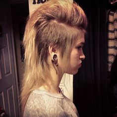 Mohawk for girls: shaved both sides, layers on the rest of hair, leaving the back long. Start teasing at the front working your way through too the back using a lot of hair spray after every tease!