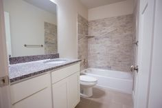 Tiled shower guest bathroom with granite countertops