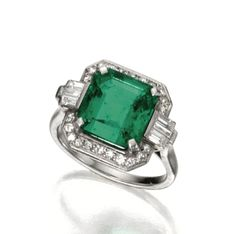 PLATINUM, EMERALD AND DIAMOND RING, CIRCA 1925    The square emerald-cut emerald measuring approximately 10.47 by 10.25 by 6.05 mm., framed by single-cut and baguette diamonds weighing approximately .50 carat,