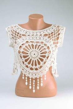 Handmade top is crocheted of cotton yarns. White delicate topic can be worn over shirts and T-shirts. This article of clothing is able to