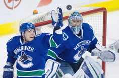 Vancouver Canucks' goalie Ryan Miller, right, watches the puck as Alex Burrows reaches for it during the second period of an NHL hockey game against the Colorado Avalanche in Vancouver, B.C., on Sunday February 21, 2016.