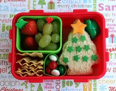 Packed in a bento box as rosy as Santa's cheeks is a green dish of strawberries and grapes, a Christmas tree sandwich (decorated with cheese star and sprinkles), some SunChips, the tiny green cup in the corner holds sunflower kernels and the pièce de résistance: heart-shaped mini cup lovingly cradling the beloved Christmas colored mint M&M's.