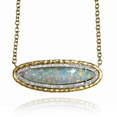 18k yellow gold with a 9.54 carat boulder opal that alters colors drastically in different lights. Opal is accented with 0.35 total carats of sparkling pave diamonds