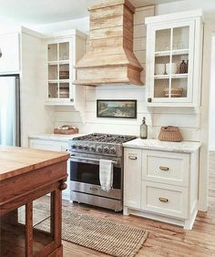 Clean white farmhouse kitchen with a reclaimed wood range hood and wood island