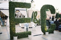 Make an entrance with towering hedges shaped like you and your beau's initials! #entryway Photography: Jose Villa Photography. Read More: https://www.insideweddings.com/weddings/incredible-rooftop-rehearsal-dinner-with-striking-striped-tent/555/