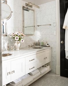 Glamorous gray and white marble master bathroom with satin nickel hardware and faucets, and a dramatic glossy black painted door.