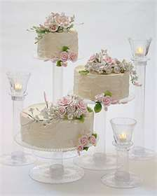 Ambiance~  To add interest and elegance to your wedding cake display, consider alternating the cakes at various heights and sizes and using elevated votive candles~  (Photo Credit: letthemeatcakeat your wedding)  (410) 819-0046  www.maryannjudy.com