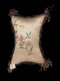 A pin cushion, roughly rectangular in shape with points somewhat elongated and finished with gold tassels, covered with white satin with gold narrow fringe around central seam, on one side a spray and garland of flowers in pins on other side a small-scale floral spray embroidered with polychrome silks. 3 15/16 x 5 5/16 in.