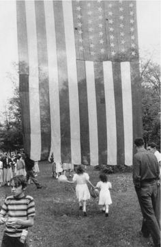 (i had more to say but it only allows 500 words) You can see people socializing on the perimeter of the frame but my eyes are led to the two little girls and the American flag. What is is interesting to me is the transparency of the American flag. Is it an old flag? Is it a new flag? It's up to your own interpretation. The flag intersects the middle of the photograph but doesn't over take the image because of it's transparency which I think is really nice.