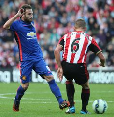 Juan Mata of Manchester United in action with Lee Cattermole of...