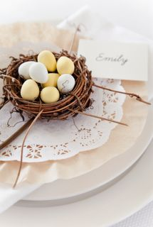 Easter placesetting.   A little bird's nest, filled with Mini Cadburry Eggs, placed on a doily, which is set on a coffee filter.