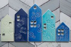 Set of 5 porcelain row houses. Slab built and stamped with my designs and stamps I got in India. Each has a sawtooth hanger on the back along with