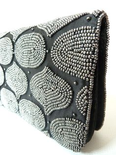 """These evening bags are the perfect essential for a black tie affair, or to make an impact statement in sandals and jeans. The Mosaic pattern is hand beaded on each of these bags, reminiscent of an Indian temple or a Morrocan Souk.  We've shot them in Natural sunlight to show their subtlety. The bags have magnetic snaps and a chain inside, plus a small satin trimmed mirror... PLEASE SPECIFY TONE OF BEADS, BRONZE OR PEWTER. 8"""" x 4"""" x 1.25"""""""