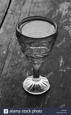 Download this stock image: vintage shot glass with vodka on an old wooden black table closeup. black and white photo - H7K85N from Alamy's library of millions of high resolution stock photos, illustrations and vectors.