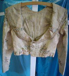Kabátek béžový dámský, střih do pasu, šálový límec s ozdobným okrajem, starý fond muzea Chomutov. Sbírka Oblastního muzea v Chomutově