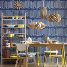 Bold geometric wallpaper is the basis for this retro scheme. The wooden pendant lights grouped low over the dining table echo the retro wooden furniture.