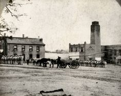 """Prison yard at the Texas Department of Corrections, Walls Unit, in Huntsville, Texas. 1873-1875. Prison inmates in striped uniforms stand in lines approaching one of several buildings. A steer-drawn wagon is in the center of the prison yard. George Fuermann """"Texas and Houston"""" Collection, 1836-2001. Special Collections, University of Houston Libraries (Public Domain)."""