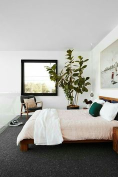 gorgeous bedroom! blush pink bedding, black framed window, large plant, arm chair, artwork over bed. LOVE!
