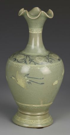 Korea, antique celadon vase, decorated with birds and auspicious symbols, flouted base, with body tapering to bulbous shoulders, with a floral motif tapering to long neck, with flouted and scalloped lip. Height 9 1/2 in.