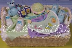 Baby gift basket cake with hand sculpted fondant bear, shoes, blocks bib, rattle and other elements.