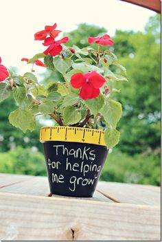 """""""I painted some clay pots (all supplies from where else, Michaels!!) with black chalk board paint, and the rim yellow. Marked out a ruler and drew the lines with a sharpie marker. The plants are from Home Depot and that's it."""""""