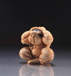 Polychromed and detailed Japanese carved netsuke, depicting a man with both hands on his head, earlyo to mid 20th century period, artist's signature to the base. Size; Height of this carving is 1 1/2 inches with width of 1 5/8 inches.