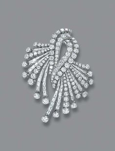 A DIAMOND BROOCH   The central twin scroll to brilliant and baguette-cut diamond sprays, each line with collet terminal, circa 1960, 6.8 cm. high