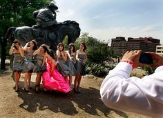 Zoe' Chavez , center, and her friends fight the wind as they have a photo taken in front of a statue at Pioneer Plaza in downtown Dallas as she celebrates her Quinceañera.