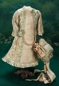 French Silk Bebe Dress and Matching Silk Bonnet. Of superb patterned pale moss green silk with interwoven design,the princess-style dress has an inset panel of ivory crepe-de-chene at the center front,border of narrow pleats at the hem,and is decorated with self-covered buttons,cope braid,and lace. With matching silk bonnet trimmed with silk flowers. Late 19th century. http://Theriaults.com/