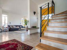 דלת צהובה קיר בטון ריצוף בטון 20/20 ומדרגות עץ