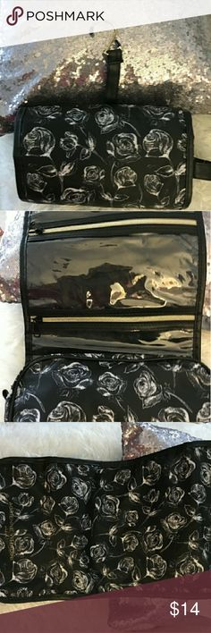 Adrienne Vittadani travel accessory foldable bag Black and white floral patterned travel bag. Has compartments with zippers to enclose items. Foldable to make smaller after products are inside. Adrienne Vittadini Accessories