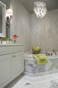 Beautiful bathroom features marble clad corner bathtub paired with marble mosaic ceiling height marble mosaic backsplash illuminated by crystal droplets chandelier situated next to white mirror mounted on large frameless vanity mirror flanked by Ruhlmann Single Sconces over white vanity topped with white marble countertops.