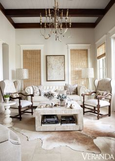Seaside style - Beachy neutral tones dictate the sunroom's serene palette. Floor lamps, Oly Studio; antique chairs in a Pindler fabric and chandelier, Tara Shaw Antiques; coffee table, Studio A through Lovelace Interiors; Roman shades from Conrad. - Veranda.com