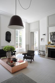 Apartment in Paris by Joseph Dirand Brass coffee table, designed by Joseph Dirand himself, Bells suspension lighting by Ronan and Erwan Bouroullec, and a plush grey Neo Wall sofa by Piero Lissoni